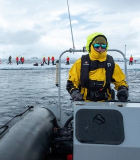 Hurtigruten Expedition Team member in a small boat (RIB) during a landing.