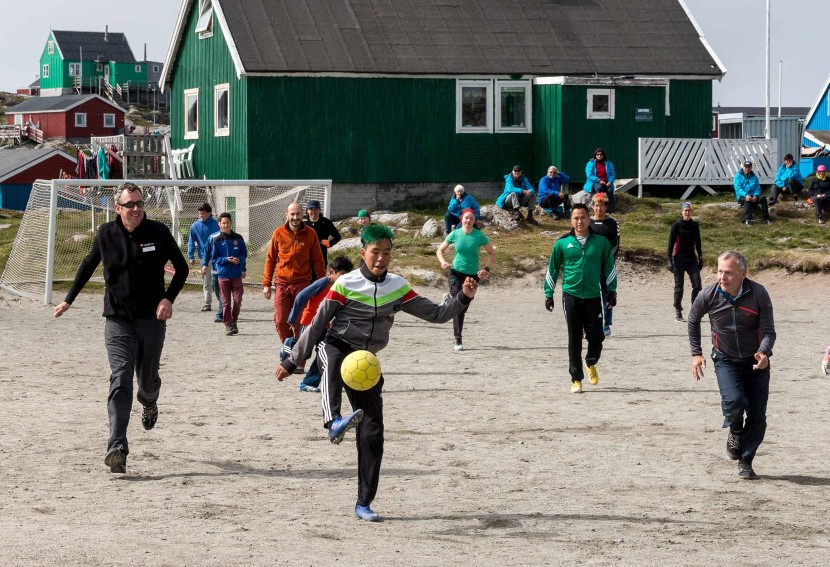 A group of people playing football on a beach
