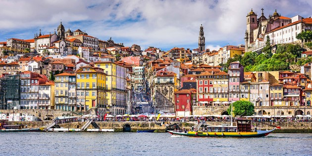 A small boat in a body of water with Porto in the background