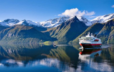Hurtigruten in Hjørundfjorden, often called the most beautiful fjord in Norway. We visit this spectacular fjord in the fall months (Sept-Oct).
