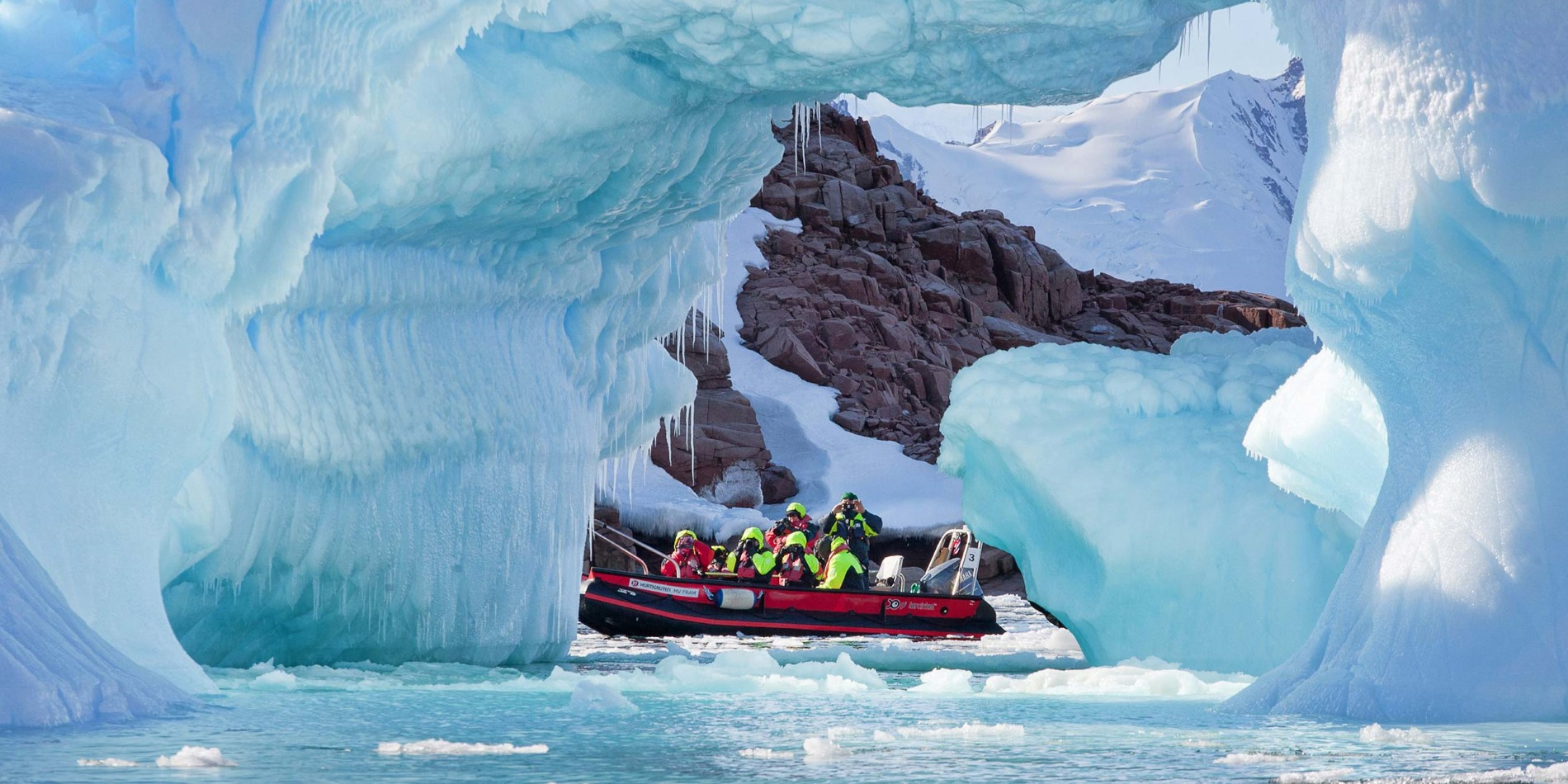Group of tourists in small boat among spectacular ice formations